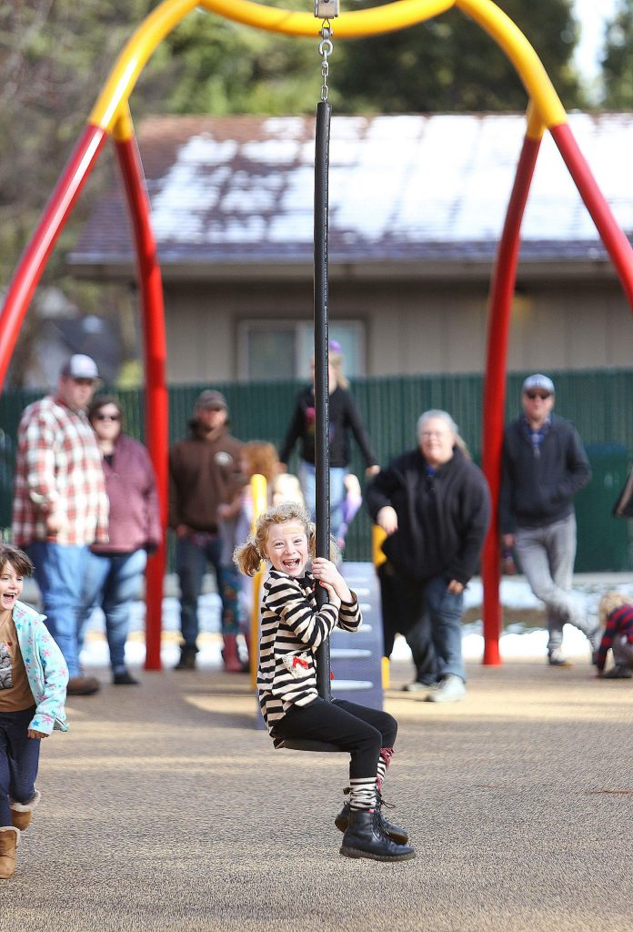 Camilla Makinson holds on tight to the popular zip line swing Saturday afternoon at recently renovated Minnie Park in Grass Valley.