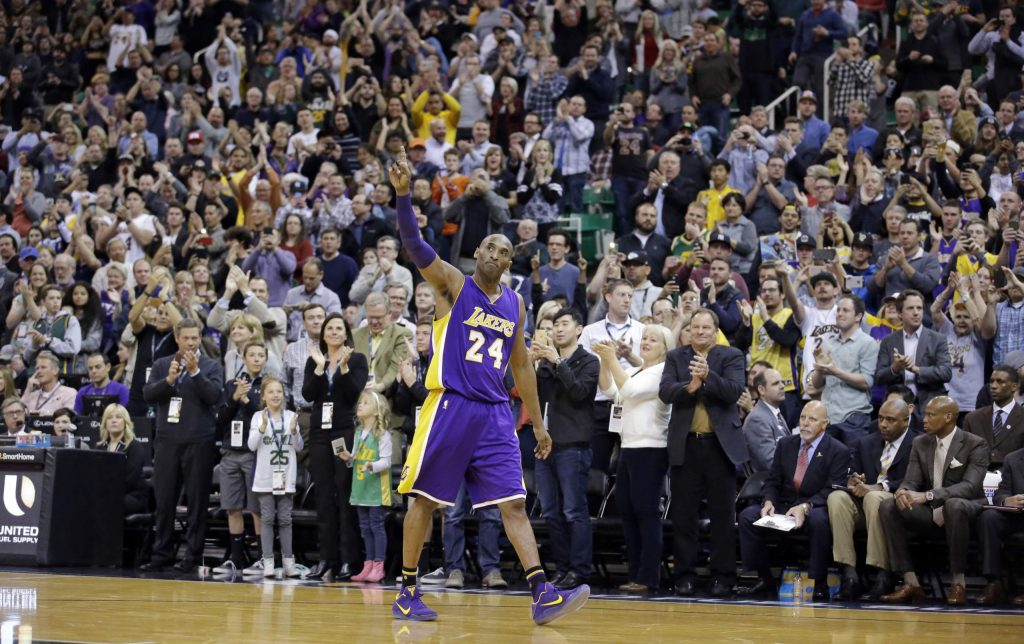 FILE - In this March 28, 2016, file photo, Los Angeles Lakers forward Kobe Bryant (24) waves as he walks off the court during the second half of an NBA basketball game in Salt Lake City. Bryant, the 18-time NBA All-Star who won five championships and became one of the greatest basketball players of his generation during a 20-year career with the Los Angeles Lakers, died in a helicopter crash Sunday.
