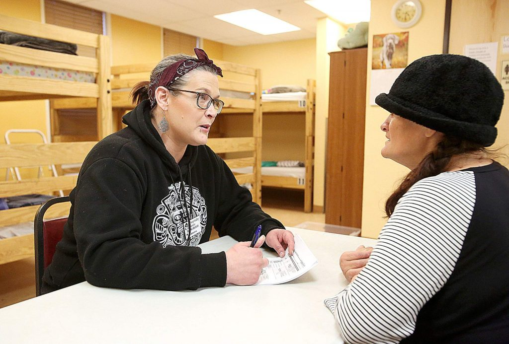 Lead shelter advocate at Hospitality House, Johanna Greene, goes over the point-in-time questionnaire with shelter client Christine Gutierrez Wednesday evening.