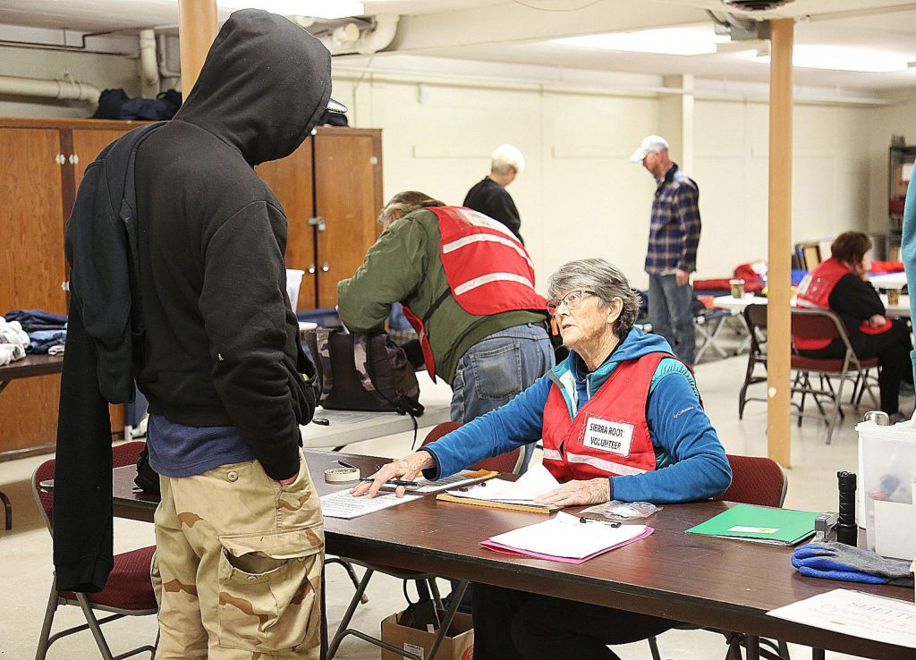 Alice Litton — Sierra Roots board member, cold weather shelter volunteer and homeless advocate — helps to check people in at the Nevada City Veterans Hall off North Pine Street Wednesday. The emergency weather shelter was enacted in part to help count the homeless for the point-in-time count.