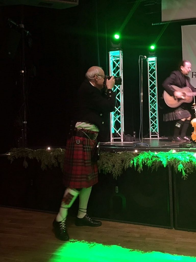 """A member of the Gold Country Celtic Society is taking a picture of """"Golden Bough,"""" during their concert at Robert Burns Night."""