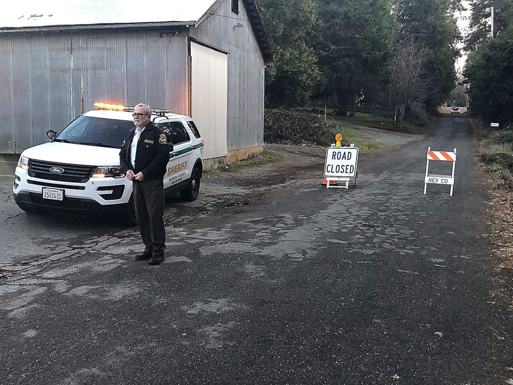 A Nevada County Sheriff's Office volunteer stands beside two signs meant to barricade people from entering Oak Street from Squirrel Creek Road. A news release states that around 1 p.m. New Year's Day a man was shot by Nevada County authorities. The man later died at Sierra Nevada Memorial Hospital.
