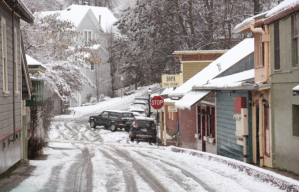 Vehicles navigate the slushy streets of downtown Nevada City during Thursday's snow.