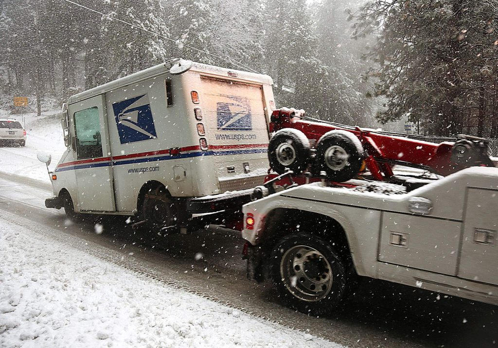 A postal service truck is towed off of Banner Lava Cap Road Thursday.