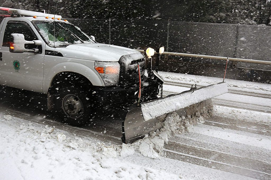 A snowplow makes its way along the Banner Lava Cap overpass at Highway 49 Thursday.