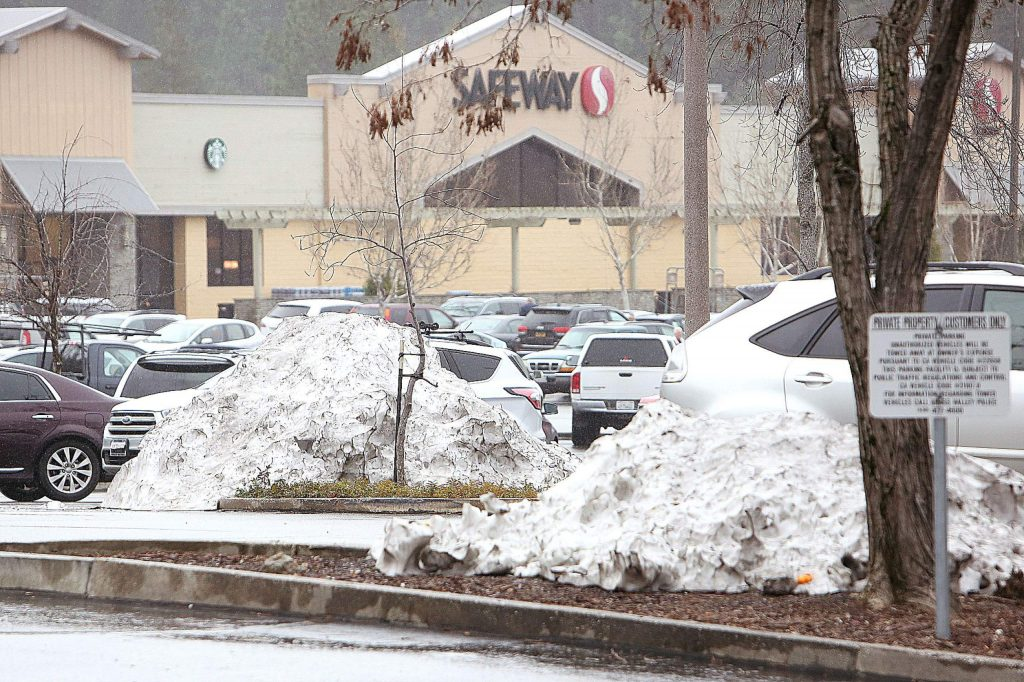 Drivers navigate parking lot glaciers as the snowfall from last week's storm slowly melts away in Tuesday's afternoon rain. A 30% chance of rain is forecast for this morning.