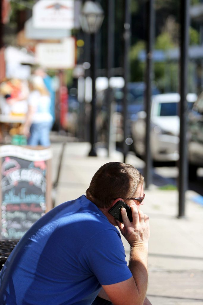 A cellular phone user makes a call at the corner of Pine and Broad Streets in downtown Nevada City.