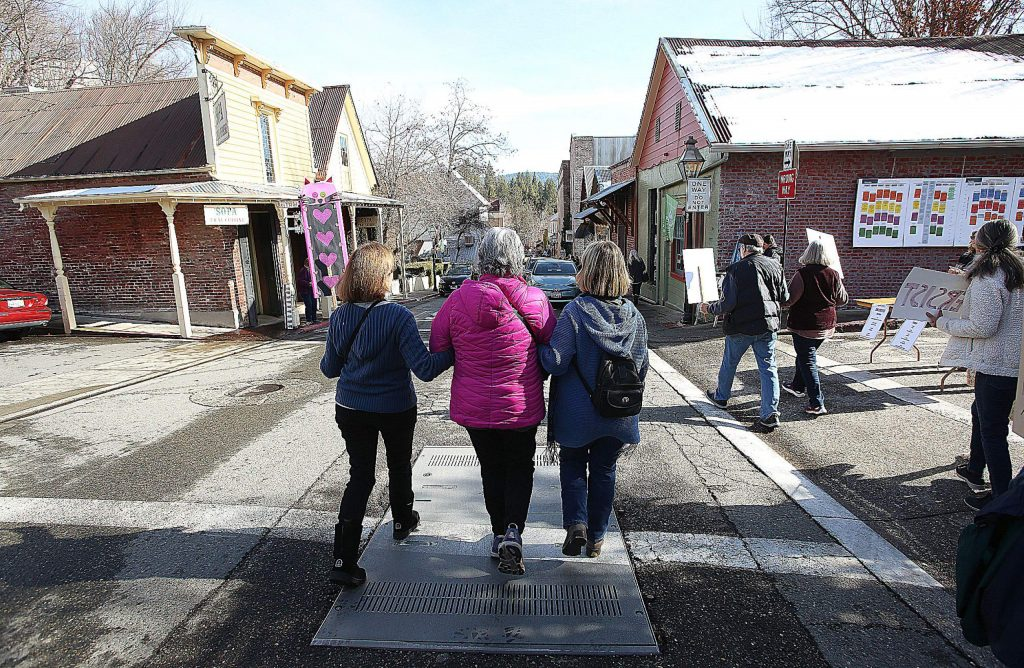 A trio of women walk arm in arm down Commercial Street in Nevada City during the women's march.