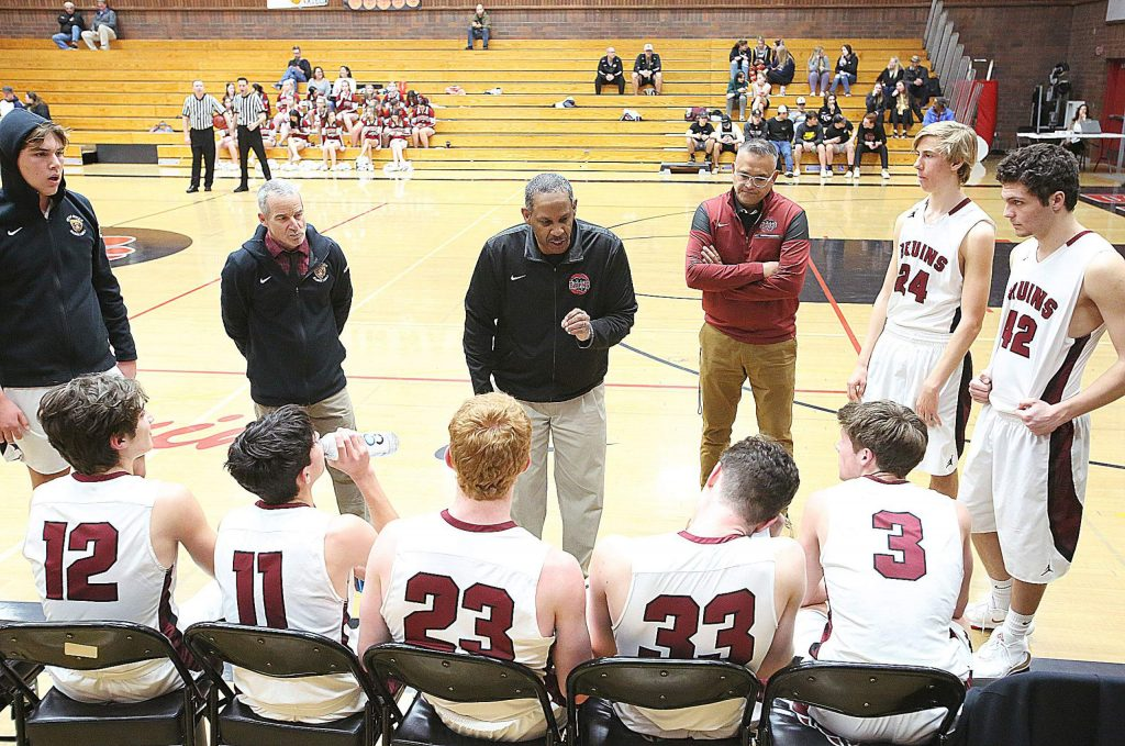 Bruins varsity boys basketball head coach Ralph Lewis talks to his team during a time out against Center.