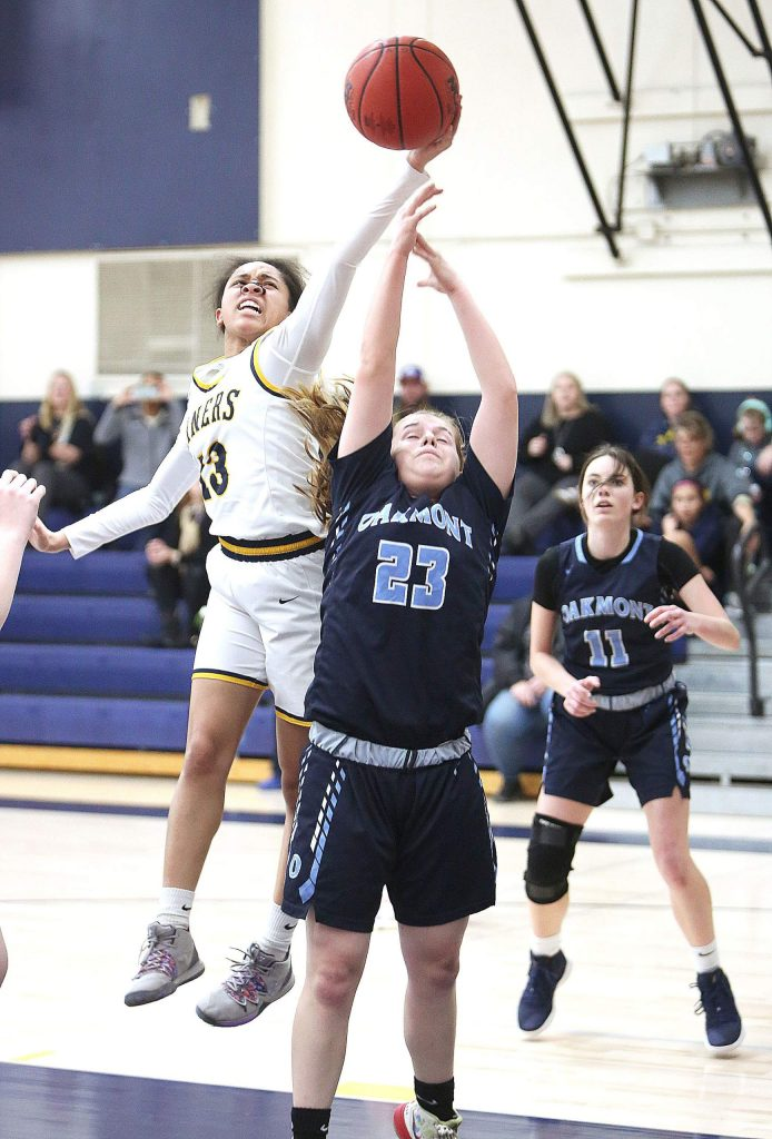 Nevada Union junior Aijah King (13) shows off her athleticism as she pulls a rebound away from an Oakmont defender.