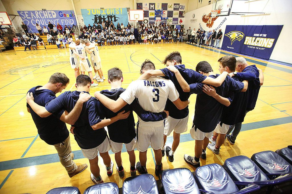 The Forest Lake Christian varsity boys basketball team comes together for a prayer before the beginning of Friday night's homecoming game against the Futures High School Knights.