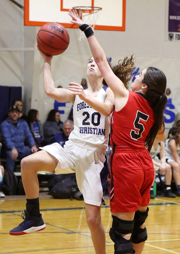 Forest Lake Christian freshman Sadie Whaley (20) banks in two points while Futures' Michelle Ivanov (5) looks to defend.
