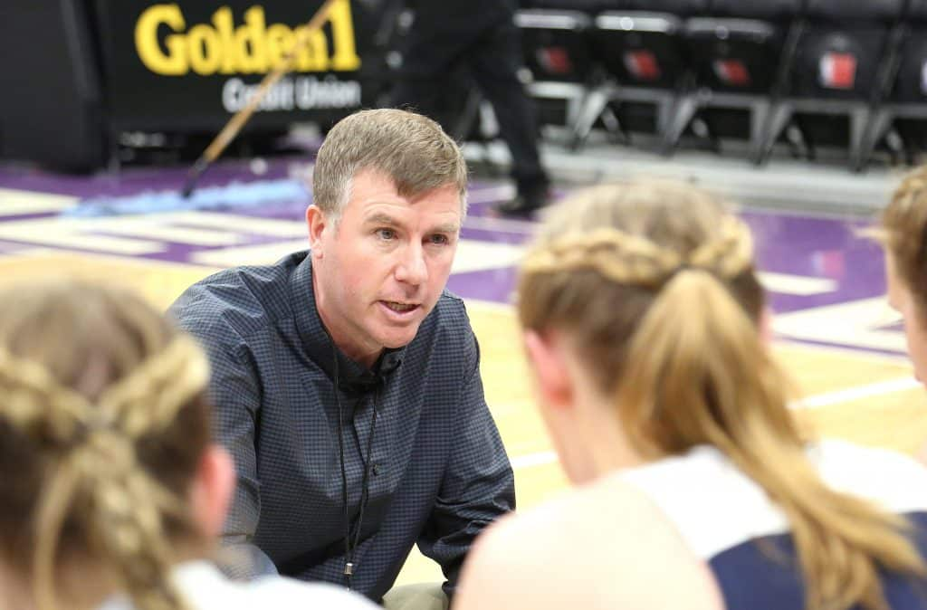 Forest Lake Christian varsity girls basketball head coach John McDaniel talks to his players during a time out.