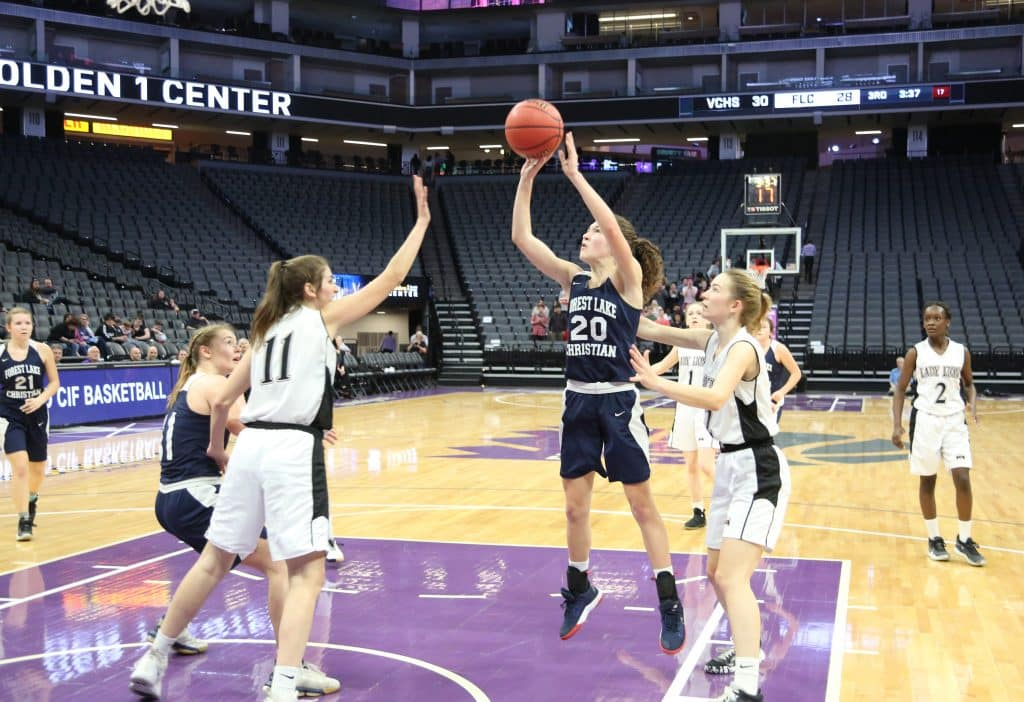 Forest Lake Christian freshman Sadie Whaley (20) takes a jump shot from the paint while being defended by the Valley Christian Lions during ThursdayÕs championship game.