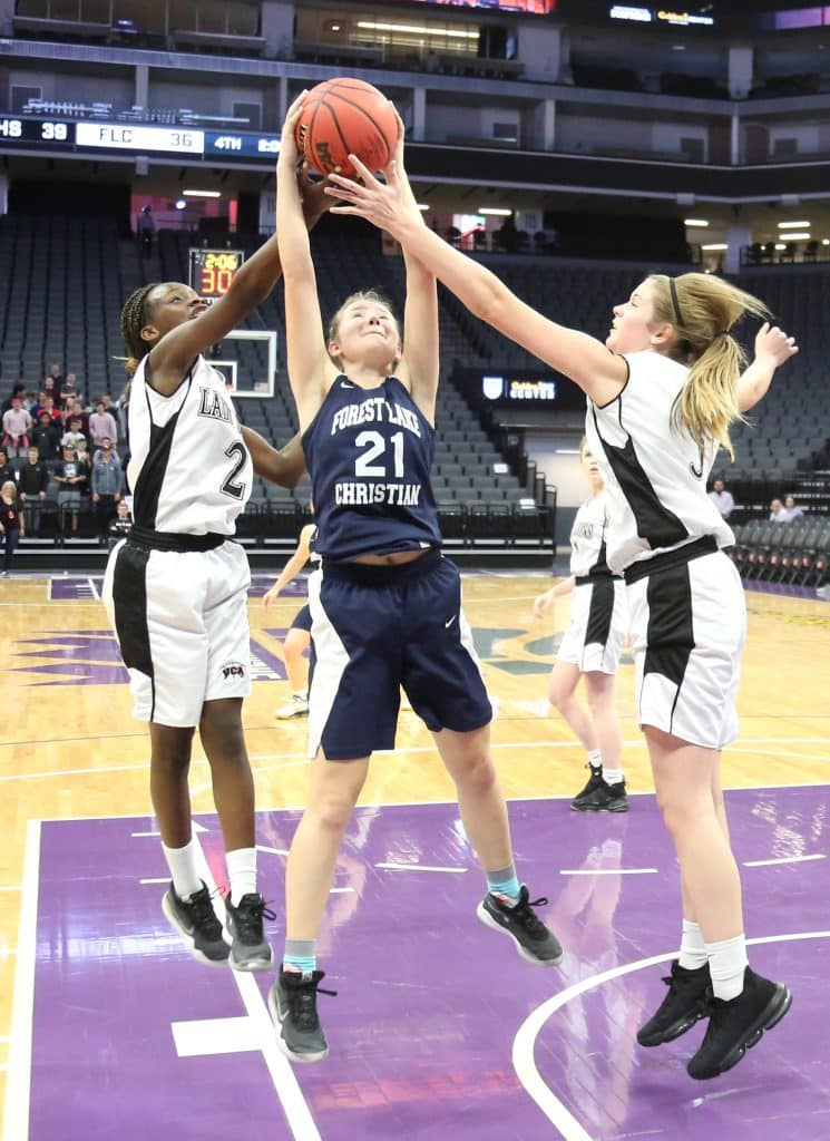 Forest Lake Christian's Ellie Wood's offensive rebound is contested by a pair of Valley Christian defenders.