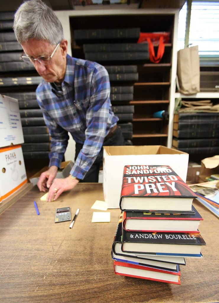 Friends of the Library book sale volunteer Barry Howard proceeds to check out a book lover's selections Saturday at the Doris Foley Historical Library in Nevada City where the monthly book sale takes place from 9 a.m. to 3 p.m.