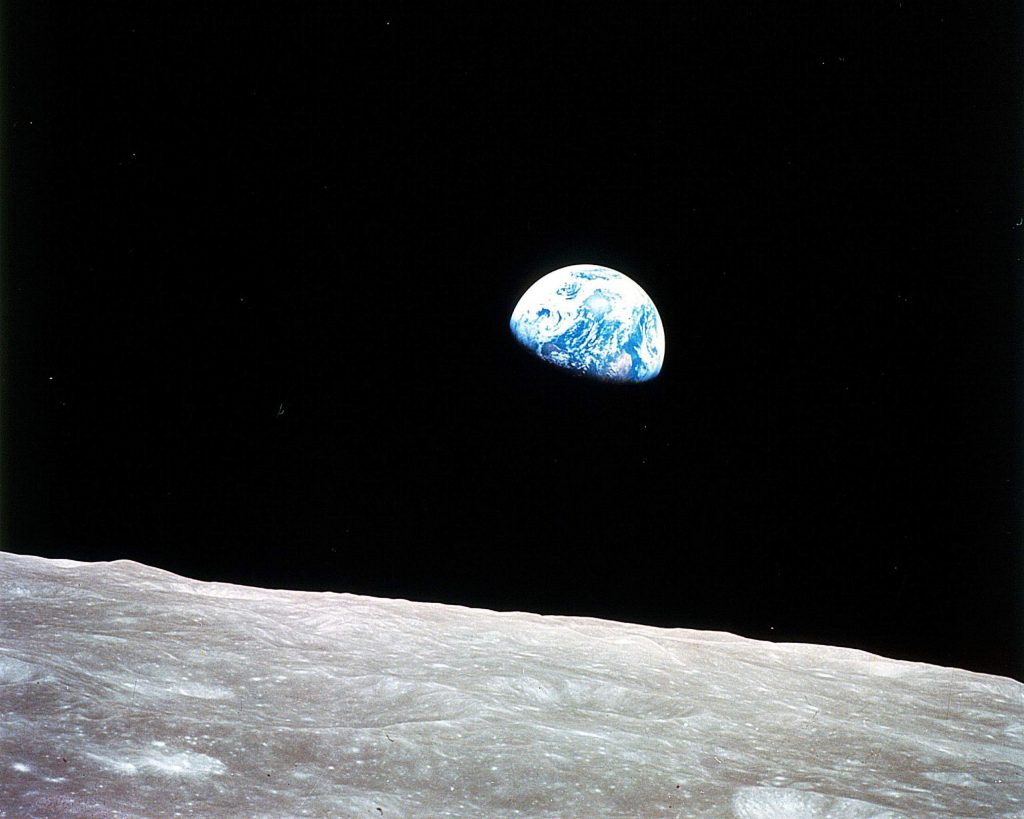Cloudy earthrise over the moon.