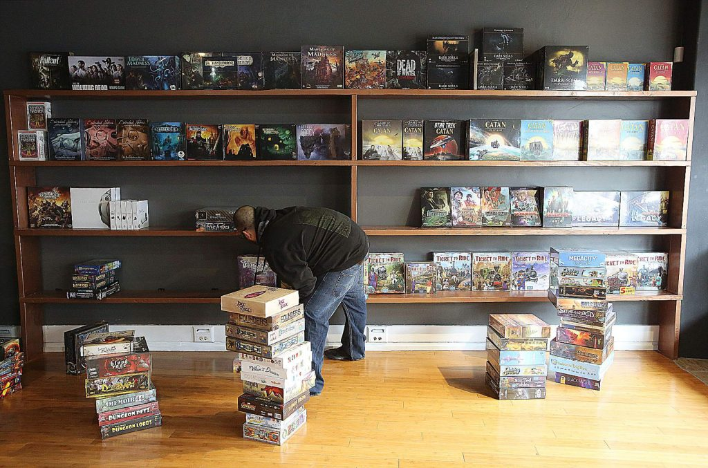 Grass Valley Games' owner Zak Lewis stocks shelves Wednesday at his store's expanded new location on Mill Street.