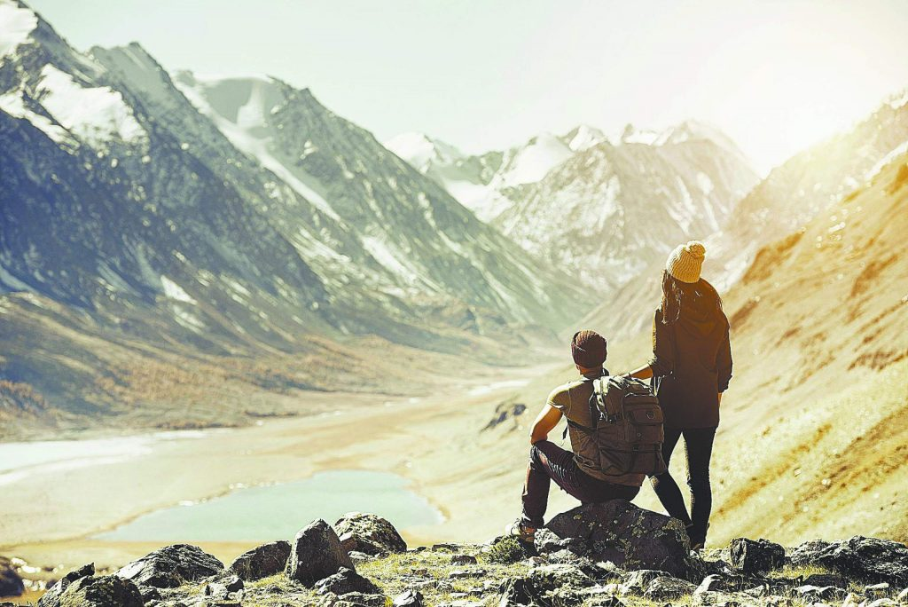 Couple having rest on mountain's top. Trekking travel concept. Space for text