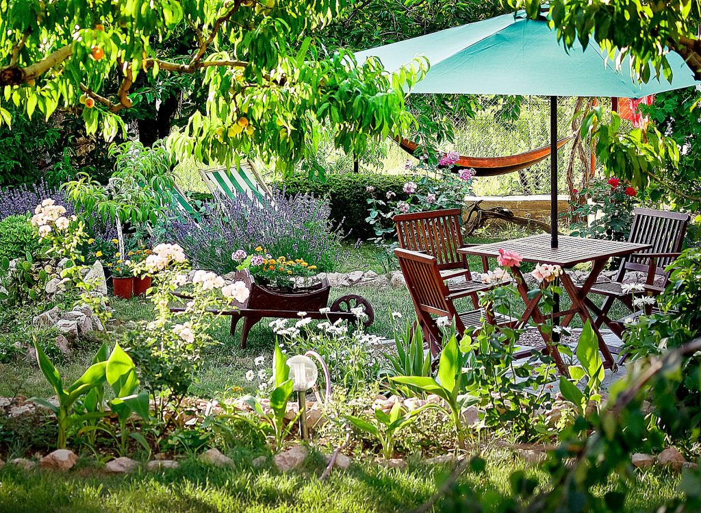 Wooden table and chairs in a beautiful garden. Landscape design of country houses. Chairs and place under an umbrella in the garden under the trees in flower beds.