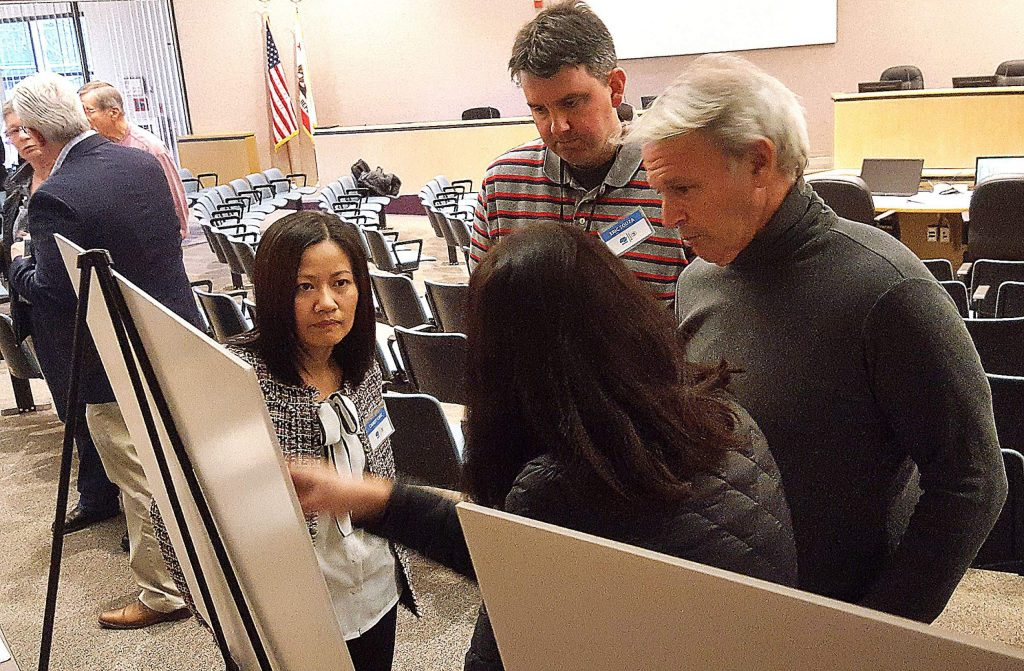 Caltrans Project Engineer Candy Chiu, left, and Design Engineer Eric Souza discuss the accident rates on Highway 20 at Lowell Hill with residents Thomas and Robin Ziv at the Monday workshop.
