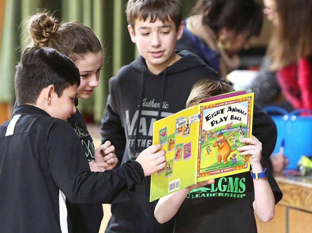 A group of youngsters have their heads stuck in a book that they plan to read to other children during Wednesday's literacy fair.