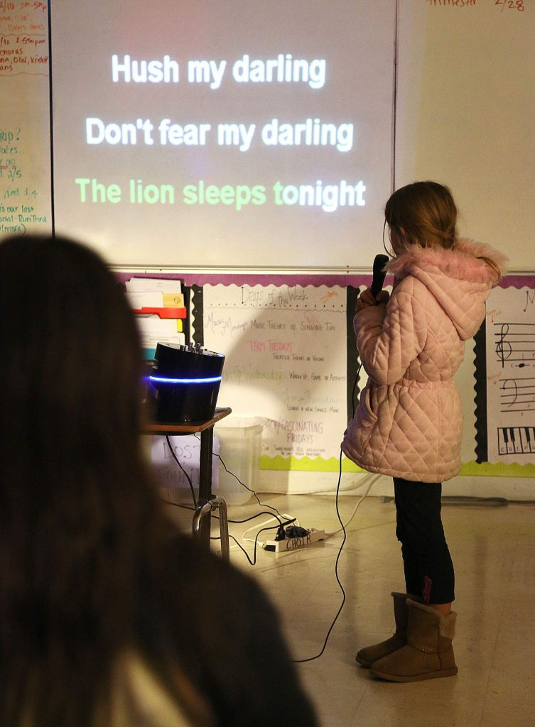 An aspiring singer reads the words from the song, The Lion Sleeps Tonight during a karaoke session meant to help kids read at the Grass Valley School District's Family Literacy Night.