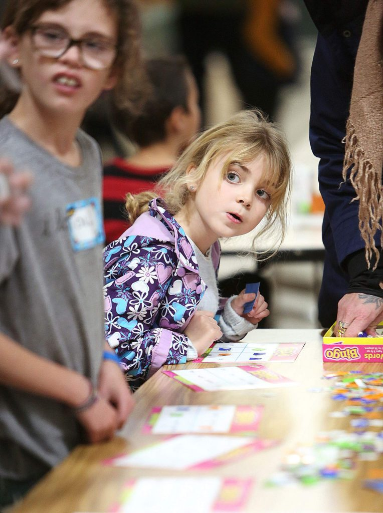 A youngster awaits the calling of a specific word needed to help complete a word bingo card during an event aiming to help students and families with literacy.
