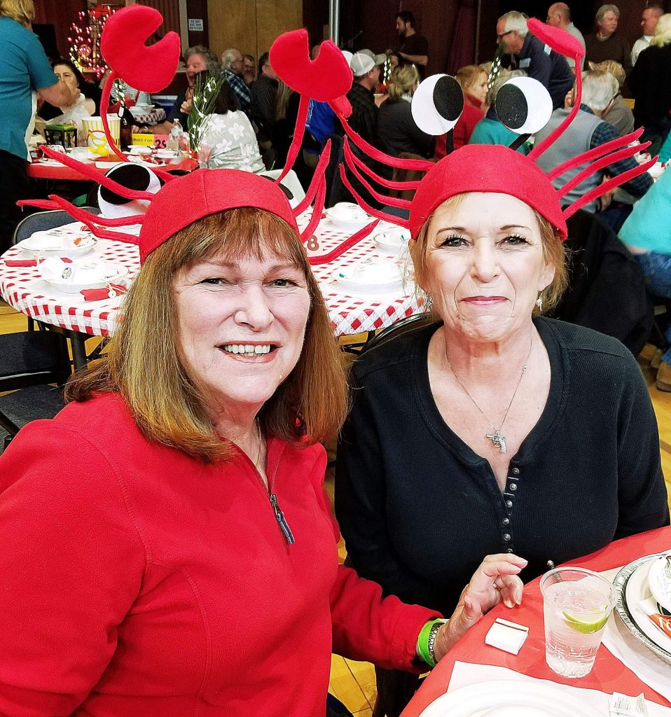 Karen Schmidt Ling, left, and Cherie Busard donned crab hats at the Grass Valley Sportsmen's Club Crab Feed. They said they appreciated the dedicated servers from the Nevada Union High School Miners football team.