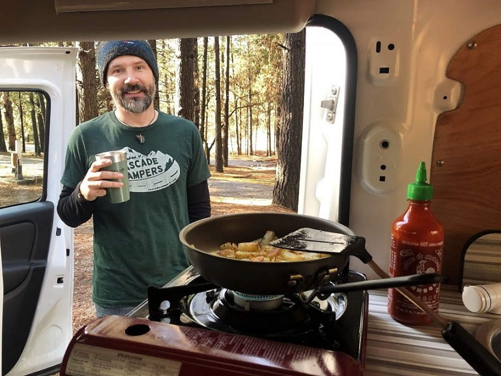 Zach Yeager, founder and co-owner of Cascade Campers in Grass Valley, cooks up breakfast in one of his vans.