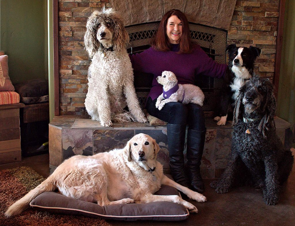 "Pet psychic Ursela Rabe is shown here with ""the kids,"" four dogs owned by Mel Marshall and Julie Morse of Nevada City. Clockwise, from the upper right, are Jackson (who was ""lost"" in the back of their car), Whaler, Cosmo and Wally. In Rabe's lap is Marcel, her special-needs rescue dog."