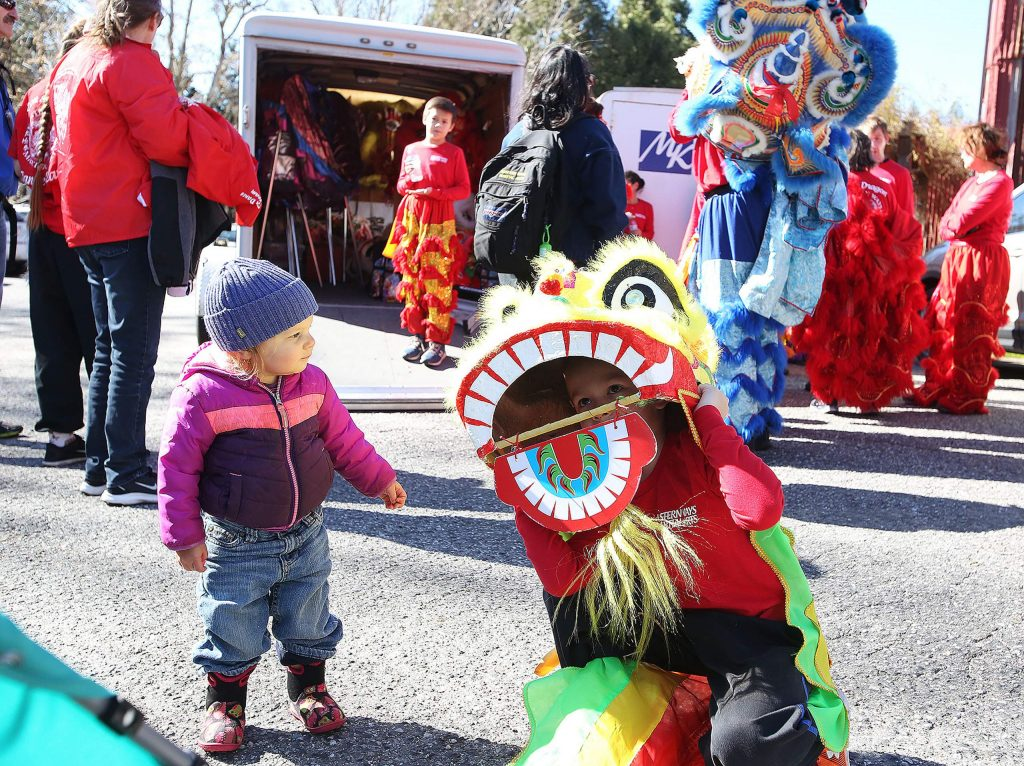 Zea 2, of Nevada Cty gets a little curious of Eastern Ways Martial Arts' Alex Dunng and his lion costume.