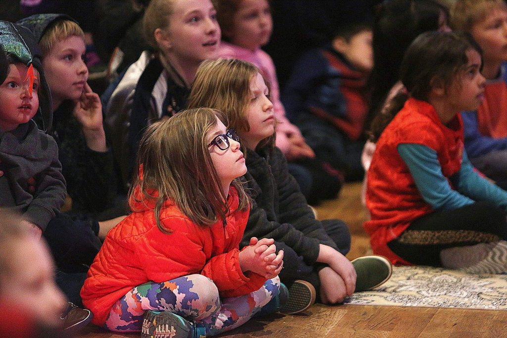 A front row of children watch as Grass Valley Taiko beat their drums.