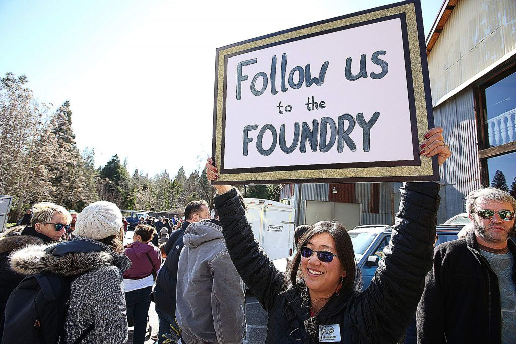 Community Asian Theatre of the Sierra board member Allison Chan holds a sign leading folks to the Miners Foundry for the Chinese Lunar New Year Festival.