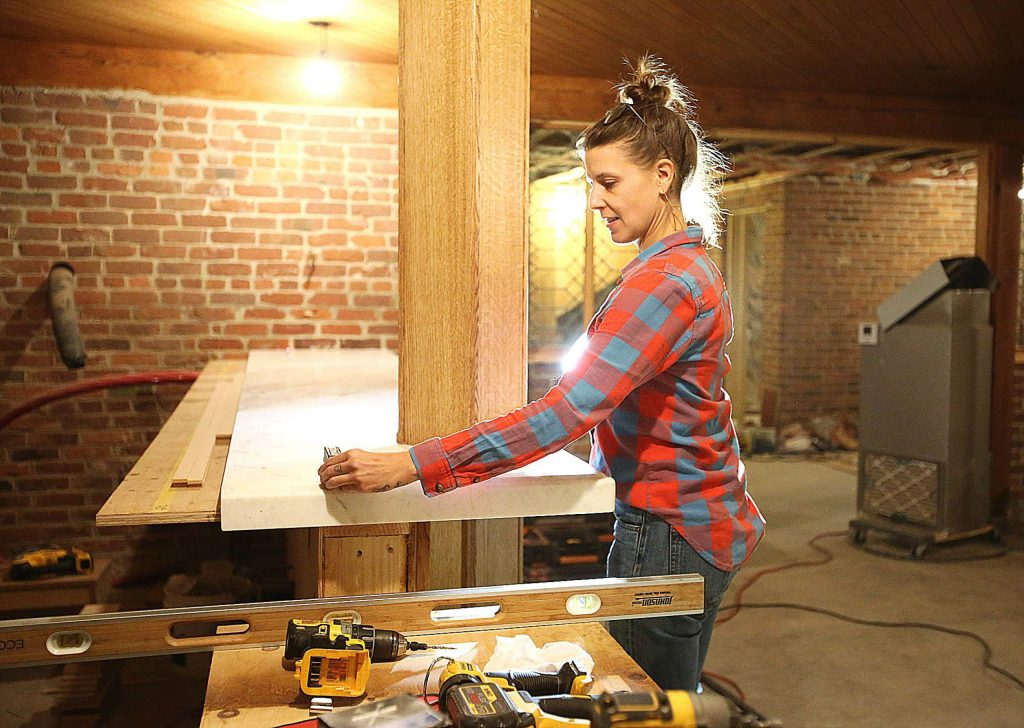 Acme Hospitality project manager Anne L'Esperance uses a laser level to make sure that new counter tops in the old Iron Door Saloon have been properly installed in the basement of the Holbrooke as restoration work continued earlier last month.