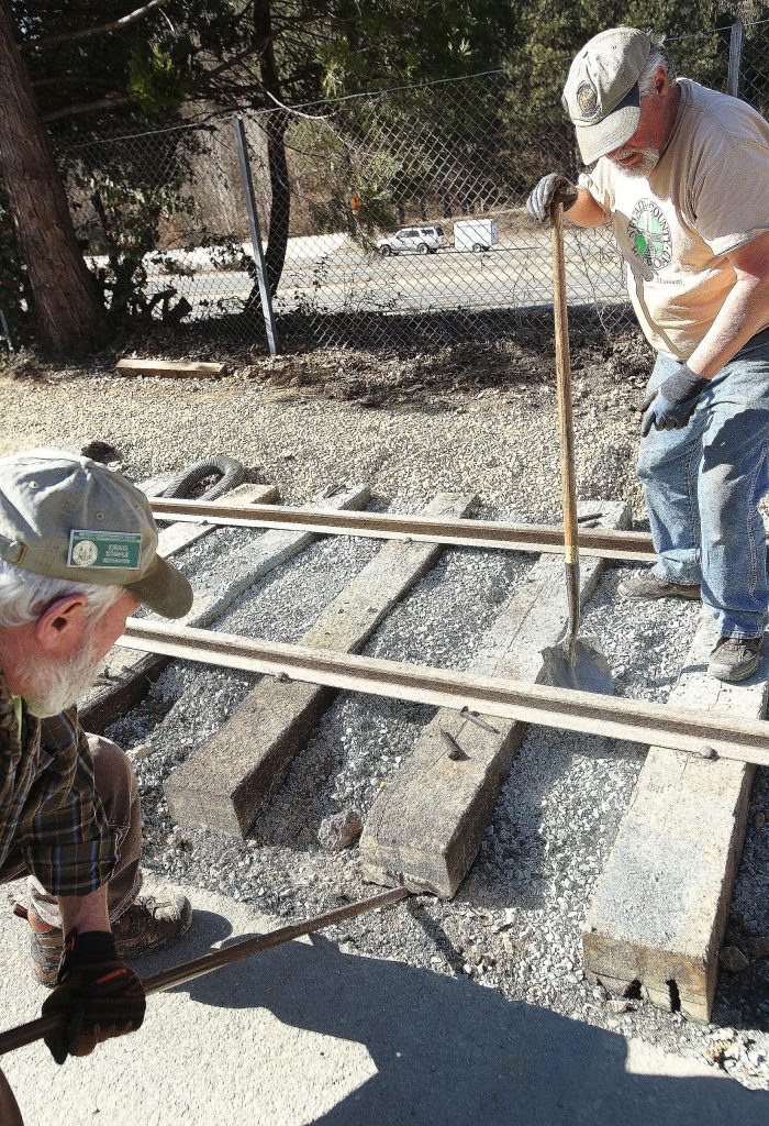 Nevada County Narrow Gauge Railroad volunteers Craig Stahle and Dana Milner work on adjusting the 300 foot track of display track being constructed along Sacramento Street.
