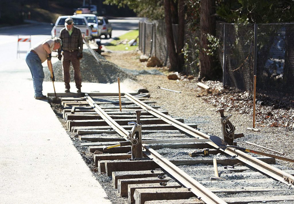 A pair of track jacks are utilized to help put the railroad ties and rails into place along a display track along Sacramento Street during a work day Saturday.