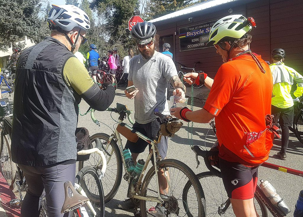 Marc Nix of Nevada City hands out Mardi Gras beads to other bicycle riders before the start of the 10th annual Jim Rogers Memorial Ride & Run.