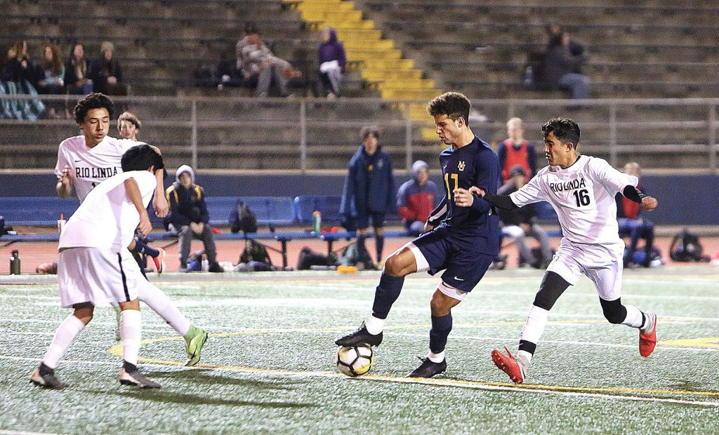 Nevada Union senior Josh Smith (17) looks to evade a trio of Rio defenders while making an attack on goal during Thursday's league win over the Knights.