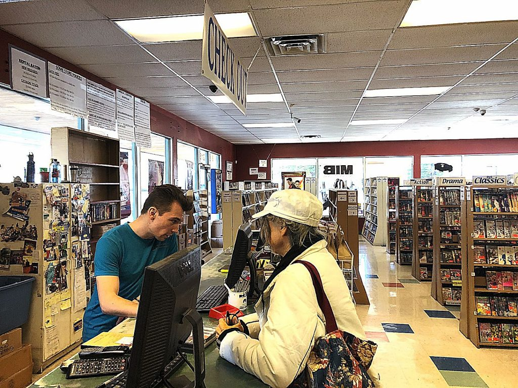 Austin Dyer helps a customer at Video Library. The store sits in the Glenbrook Basin.