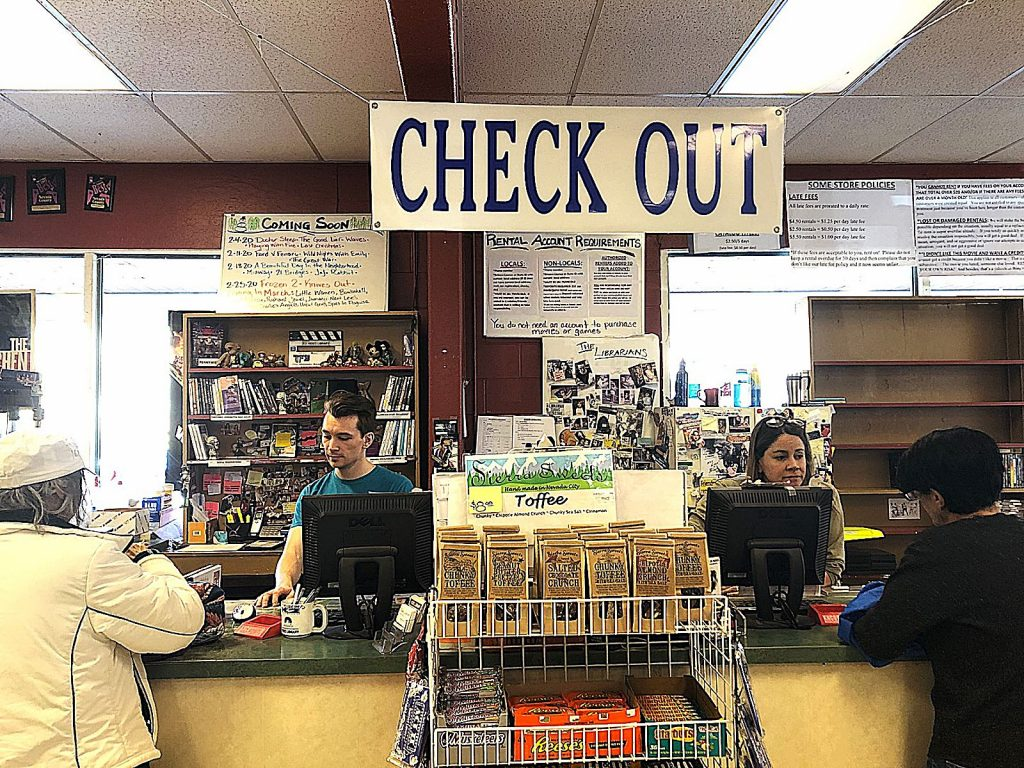 Austin Dyer, entertainment expert at Video Library, with his colleague and store manager Darcie Gerbaud help customers at the check out line. The store is holding a liquidation sale beginning March 5.