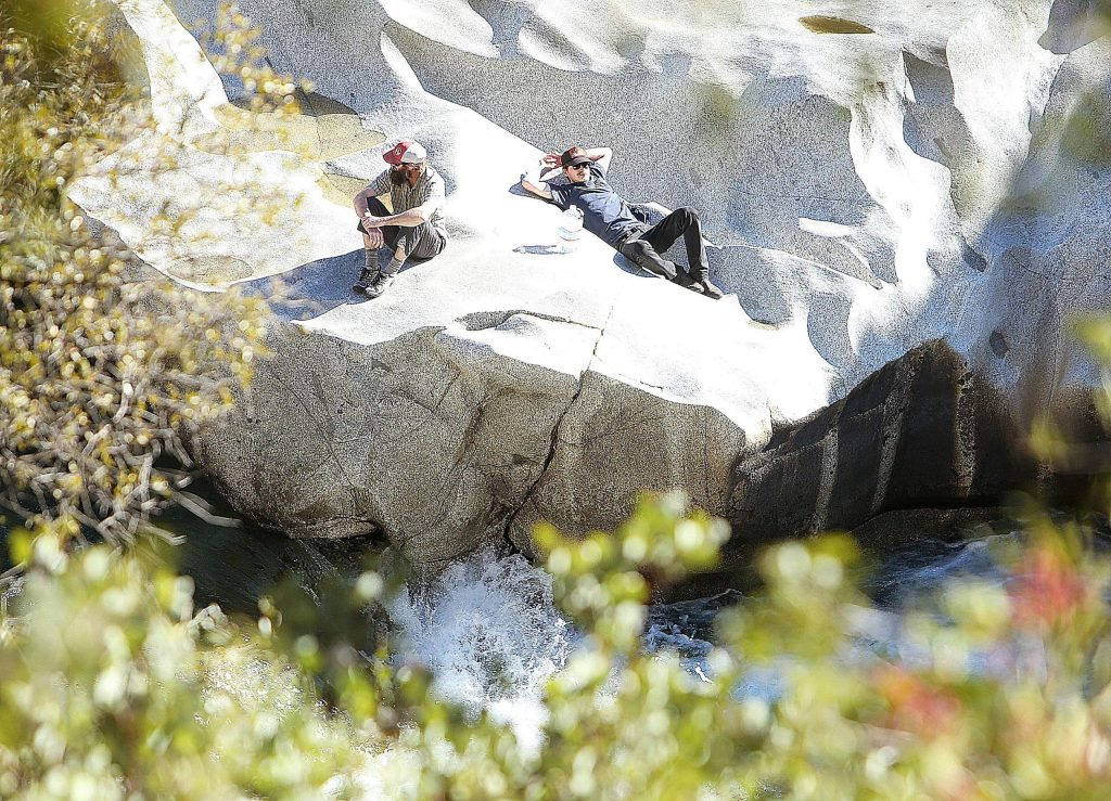 A pair of day hikers rest alongside the weathered rocks of the South Yuba River Tuesday afternoon near the Highway 49 bridge.