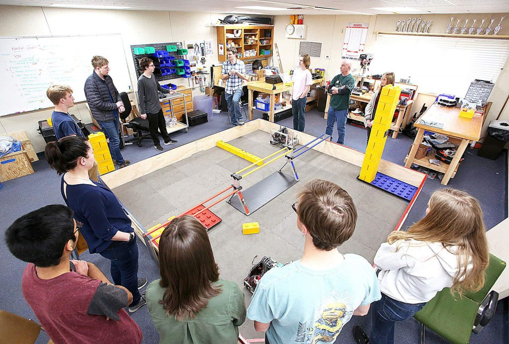 ACME and ARES high school robotics teammates gather around the robot arena before getting to work on improving their machines Tuesday afternoon at Nevada Union High School. The two teams are headed to the NorCal Championship in San Jose after recent successes.
