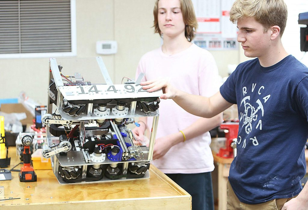 """Team ARES' Sean Giomi and Kenton Bowsell show off the underbelly of their robot """"Jank Tank""""."""