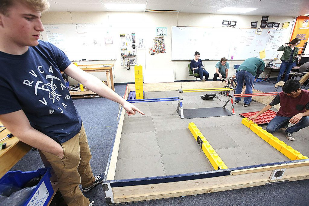Nevada Union sophomore Kenton Boswell points to the yellow bricks that a robot must pick up and stack to earn points in competition.
