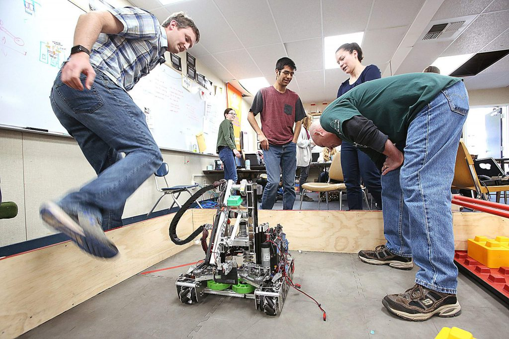 Robotics instructors take an inspection of team ACME's robot before making changes to it Tuesday at Nevada Union High School, where the team practices.