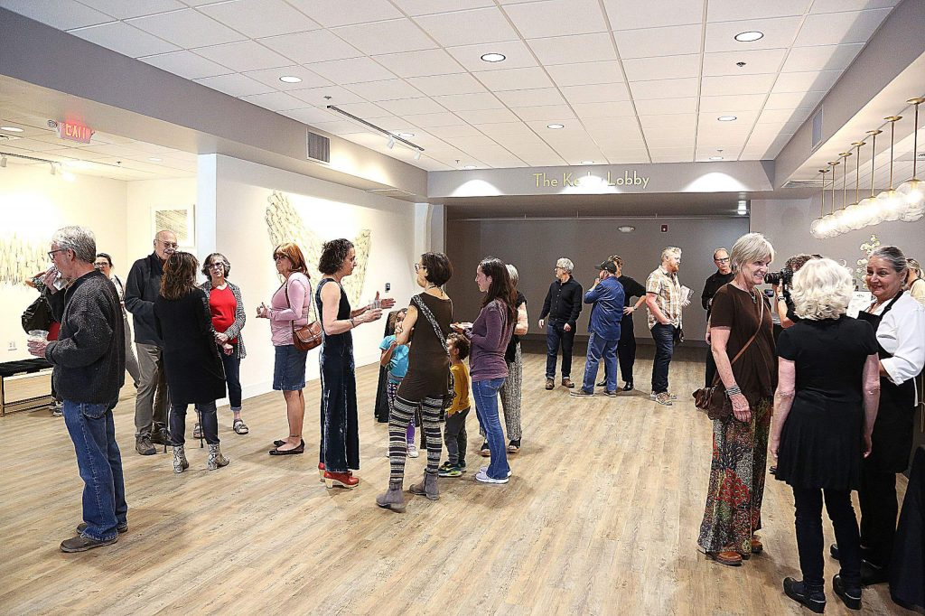Folks mingle with one another in the entry and gallery area of The Center For the Arts' recently renovated space.