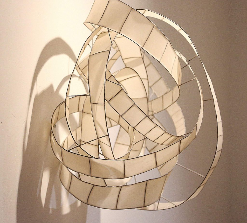 """The piece titled """"Infinite Path"""" made of copper and Japanese paper, hangs on the walls of The Center For the Arts' Granucci Gallery."""