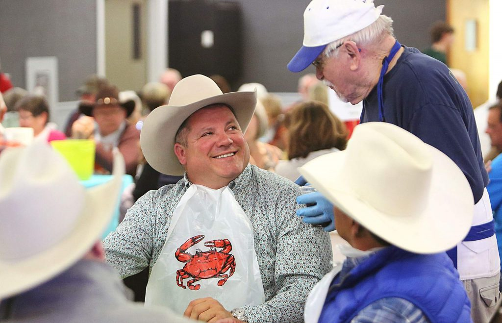 Foothill Lions Club's Arnie Romanello check on Reno Rosser's table during the Cioppino Feed Saturday at the fairgrounds. Rosser plays a big part in bringing the rodeo to the fair each year.