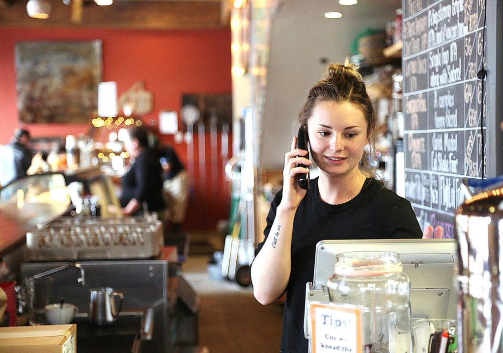 Three Forks employee Averi Linehan takes a to-go order over the phone Wednesday afternoon from behind the counter in downtown Nevada City. Area businesses such as Three Forks are offering to-go orders as well as curb-side and home deliveries in order to stay afloat during these financially uncertain times.